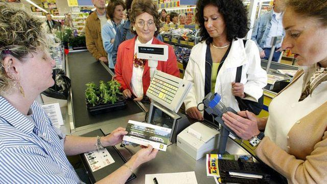 Una cajera en un supermercado atendiendo a clientes