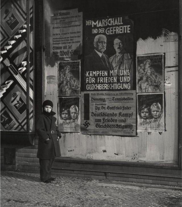 Дочь Вишняка Мара у предвыборного плаката в поддержку Поля фон Гиндебурга и Адольфа Гитлера
