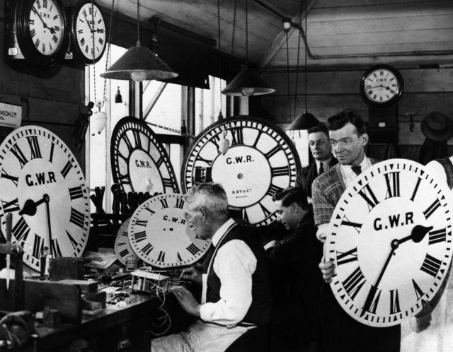 Группа сотрудников Большой западной железной дороги чинят настенные часы. 30-е годы