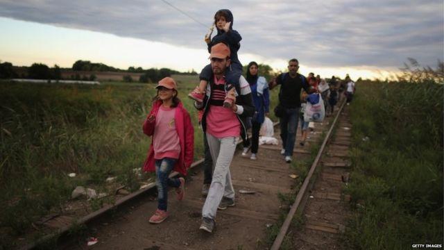 Migrants walk along railway tracks in Hungary