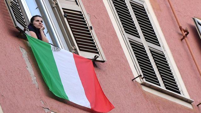 Mulher na janela, abaixo da qual se vê bandeira da Itália