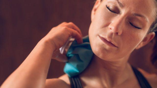 Mujer poniéndose hielo en el cuello
