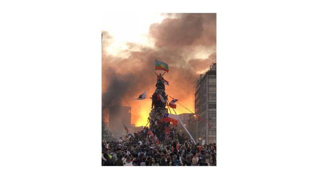 La imagen de un manifestante flameando la bandera mapuche en la cima de una estatua militar, en Santiago