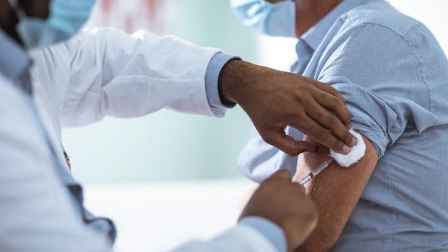 Homem sendo vacinado por profissional