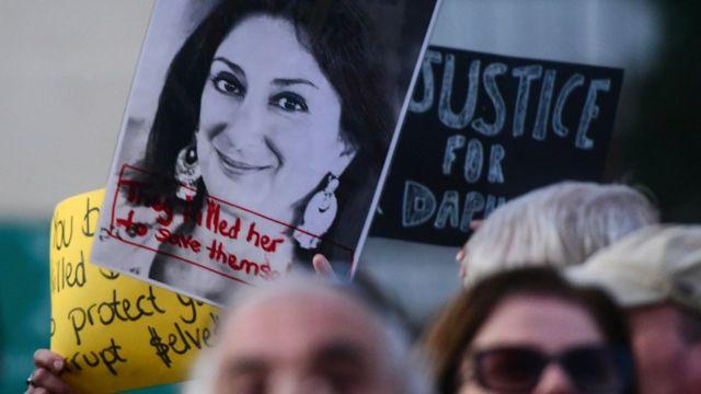 Etirazçılar öldürülən müxbir Daphne Caruana Galizia-nın fotosu olan plakat qaldırıblar