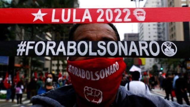 Homem segura faixas onde se lê 'Lula 2022' e 'Fora Bolsonaro'