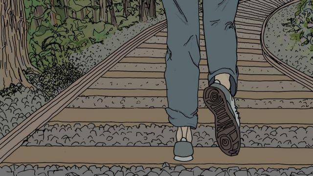 Joven corriendo sobre las vías de un tren.