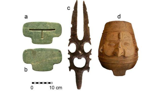 Objetos hallados en la tumba donde se encontraba el colgante, incluyendo una vasija y una escultura en piedra