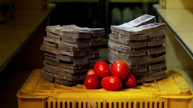 Kilo de tomates junto a bolívares.