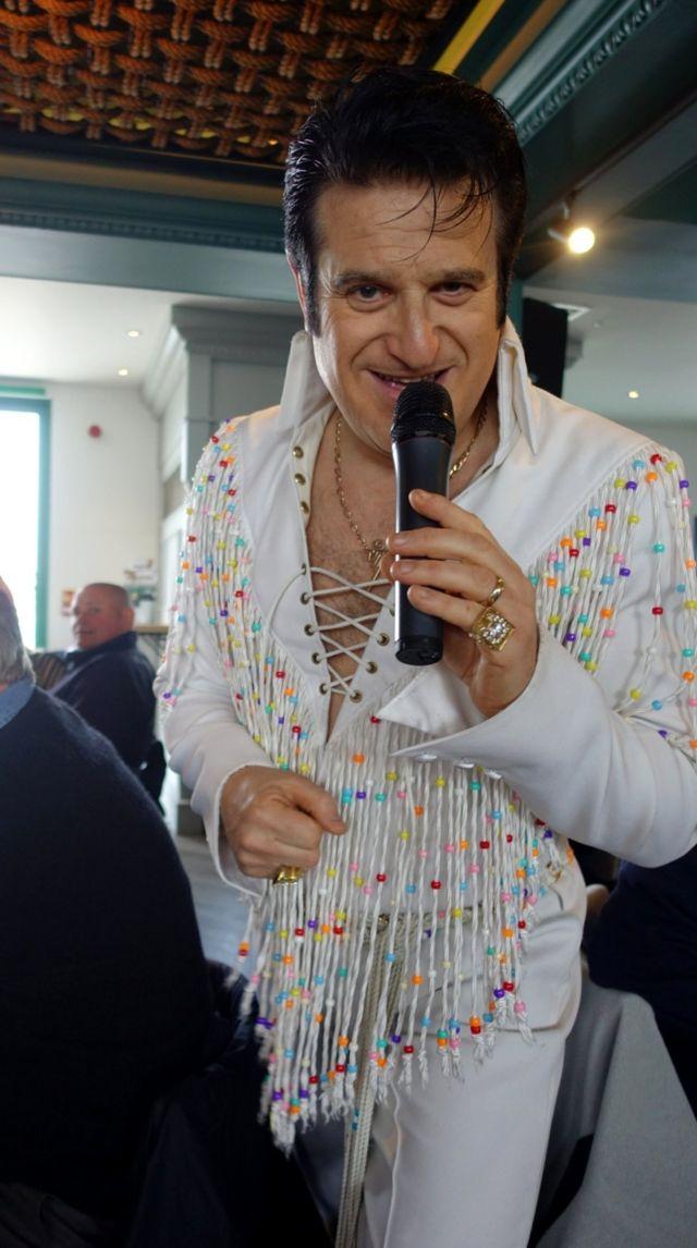 Un imitador de Elvis Presley canta con un micrófono