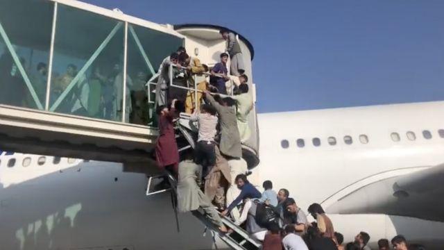 Pessoas tentam entrar em aviões para fugir
