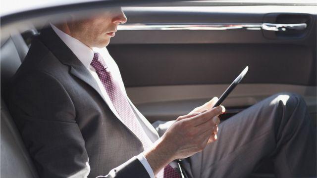 Hombre con traje leyendo en un dispositivo móvil y abordo de un auto de lujo