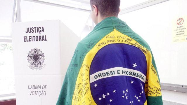 Homem envolvo em uma bandeira do Brasil se dirige à cabina de votação, em Belo Horizonte, Minas Gerais