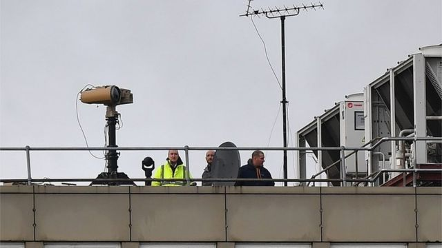 People on the roof of a Gatwick building with equipment