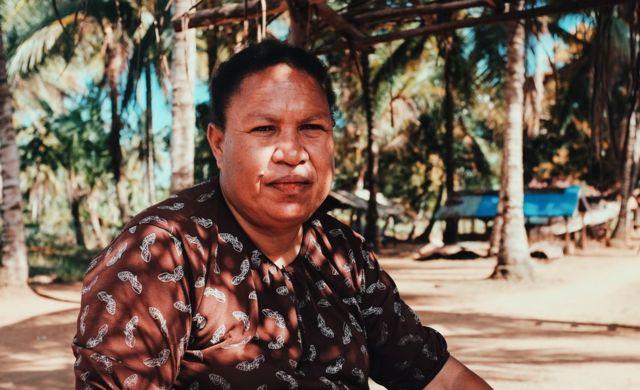 Retrato de Elisabeth Ndiwaen sob palmeiras em um dia ensolarado