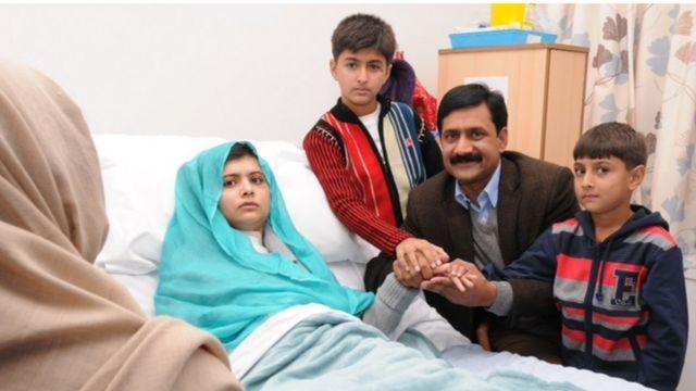 Malala em uma cama de hospital em Birmingham, cercada pela família