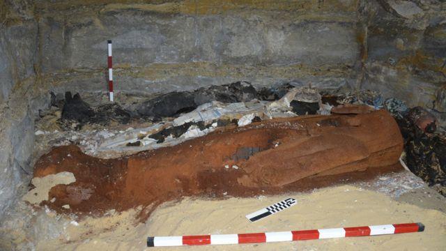 Momia hallada en Saqqara en la que puede apenas verse la máscara de plata
