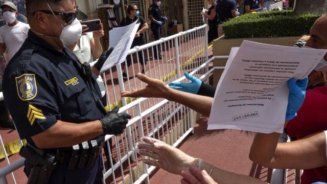 一名警察在佛罗里达州的一个停车场发放失业救济金申请表格
