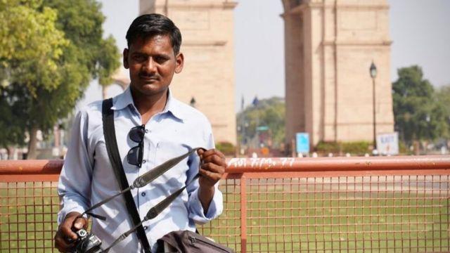 Retrato do fotógrafo Tejpal Kashya com sua câmera diante do Portão da Índia em Déli