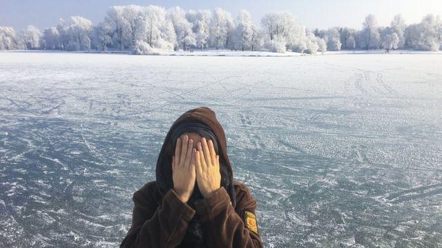 ઠંડીમાં પોતાનાં ચહેરાને ઢાંકતી મહિલા