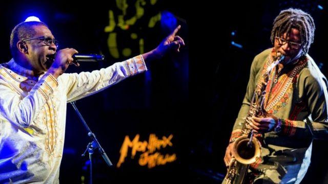 Alain Rodrigue Oyono jouant au saxophone en concert avec Youssou Ndour