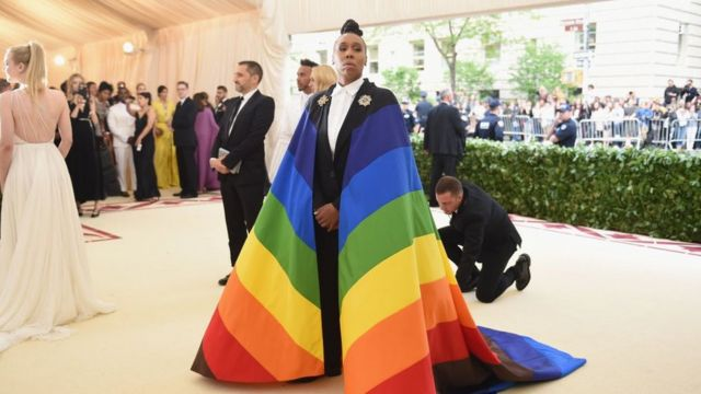 Black writer Lena Waithe wearing the Philadelphia Pride flag as a cape to the Met Gala in 2018