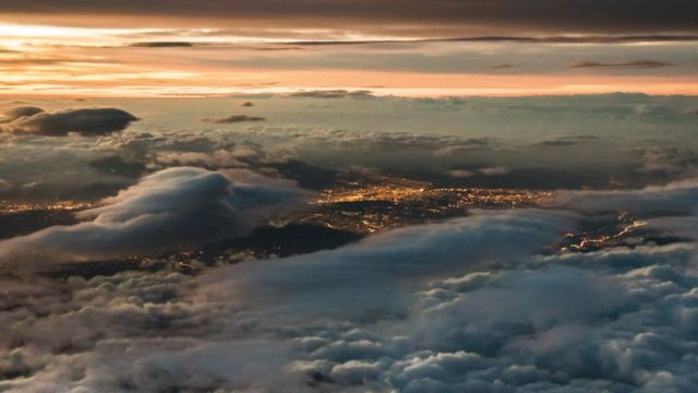 Mar de nubes blancas y un horizonte rojizo sobre las luces de una ciudad