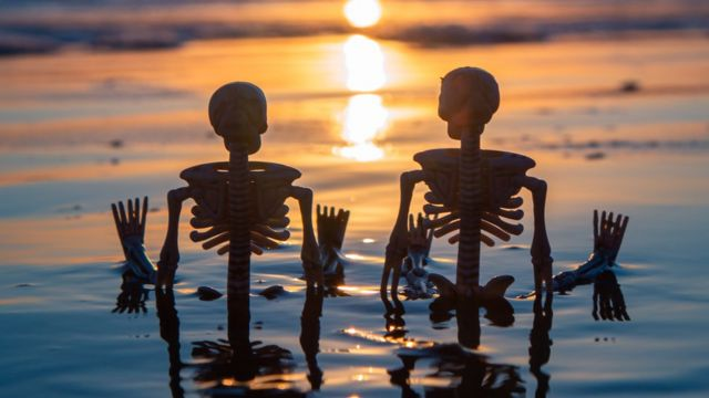 Dos esqueletos sentados en la playa.