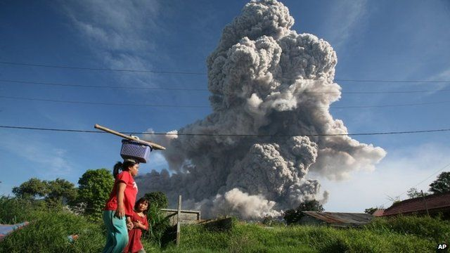 A woman and her daughter walk on a road as Mount Sinabung releases volcanic material into the air in Gamber, North Sumatra, Indonesia,