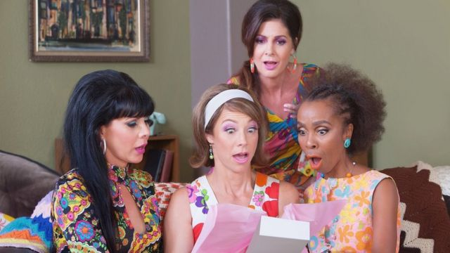 A group of female friends - the woman at the centre has a shocked expression as she opens a gift box