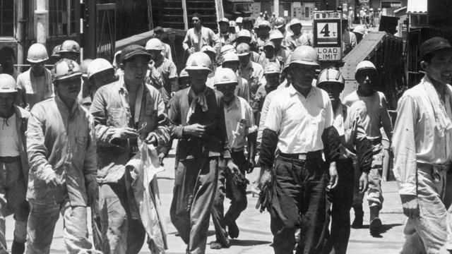 Black and white image shows Japanese workers walking down the street.