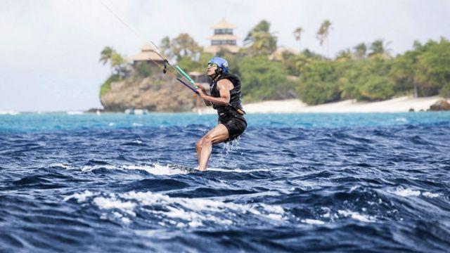 El ex presidente Barack Obama haciendo Kitesurf en el mar. Detrás de él una playa y palmeras.