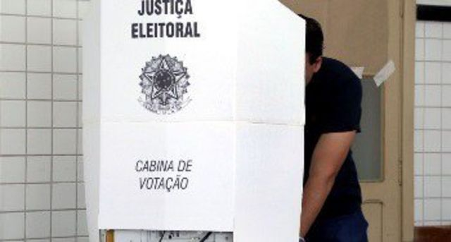 Pessoa vota em cabine de votação