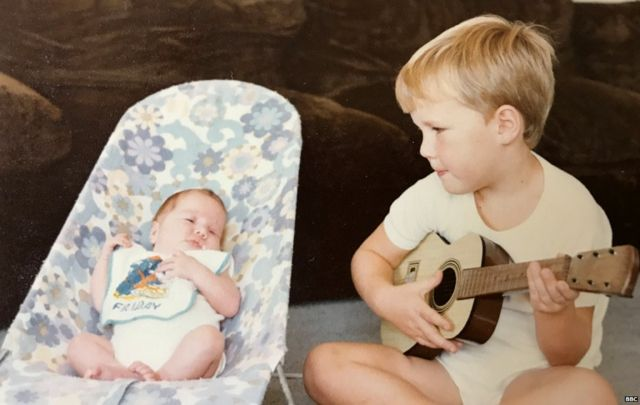 Robyn as a baby with her older brother Gareth serenading her on his guitar