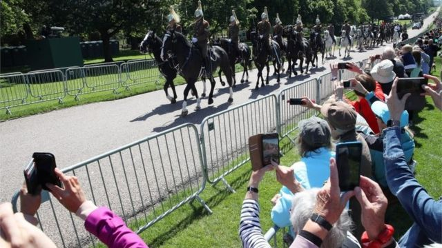 The household cavalry leads the procession as crowds capture them on their phones