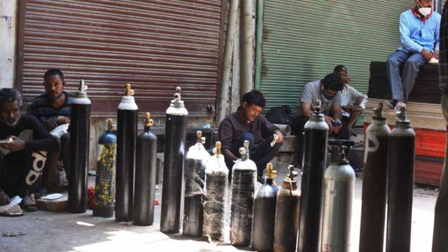 أشخاص ينتظرون الحصول على أسطوانات أكسجين وعبوات جديدة في مركز تعبئة في نيودلهي، الهند
