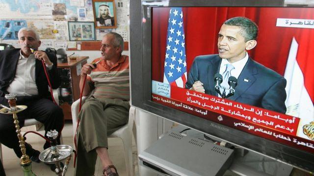Палестинцы курят кальян и слушают речь президента Обамы в каирском университете 4 июня 2009 года