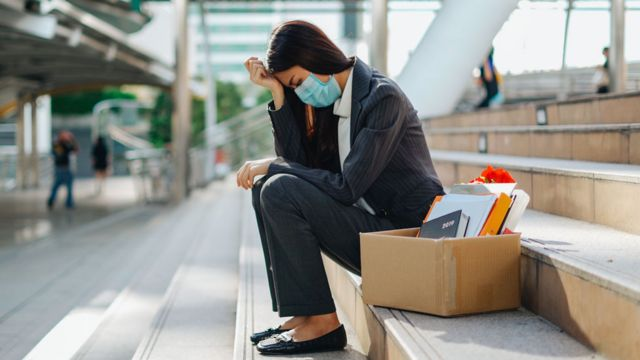 Una mujer usando una mascarilla que fue despedida