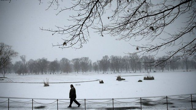 A man walks in Washington DC as snow begins to fall