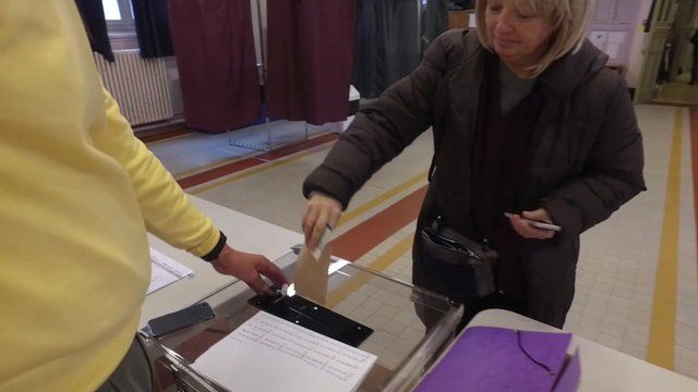 Woman casts her ballot in Paris in vote to decide the centre-right presidential candidate in next year's election