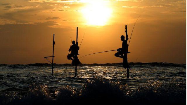 Sombras de homens pescando no meio do mar no Sri Lanka, no que aparenta ser um momento de pôr-do-sol