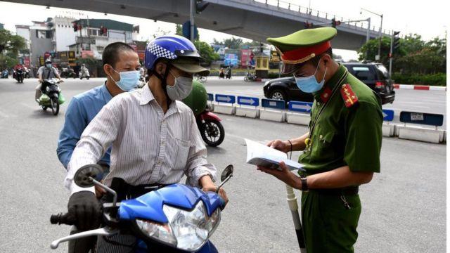 Công an kiểm tra giấy tờ một người đi đường ở Hà Nội (Hình chụp ngày 29/7)