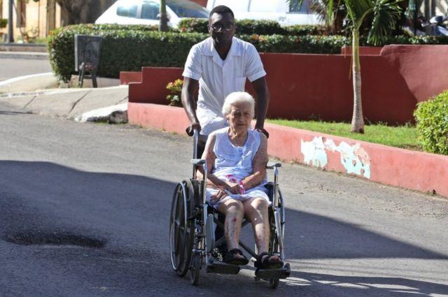 Trabajador de la salud lleva a una mujer en silla de ruedas en un hospital de La Habana.