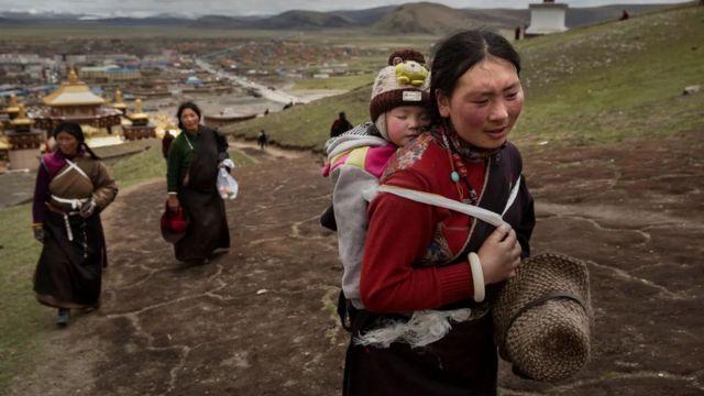 Madres orientales cargan a sus bebés en la espalda.