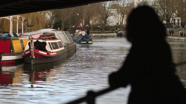 'Andrea' shown in silhouette, standing by a canal