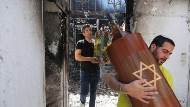 Dos hombres retiran restos de una sinagoga incendiada en Lod.
