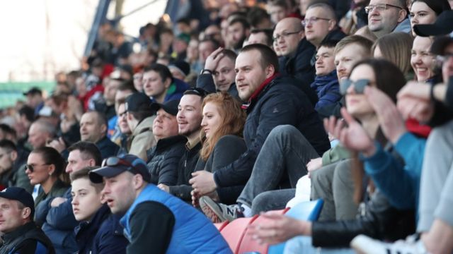 Fans cheer, as they are watching the Belarusian Premier League soccer match between FC Minsk and FC Dinamo-Minsk in Minsk o­n 28 March