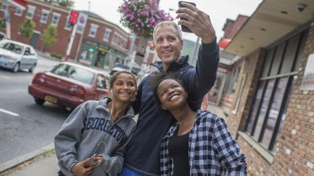 Un padre con sus dos hijas tomándose una selfie.