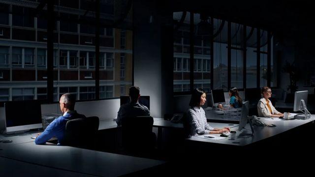 Pessoas trabalhando em um escritório escuro