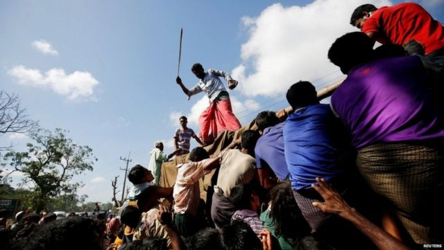A man uses a cane to control the crowd while providing relief supplies to Rohingya refugees.